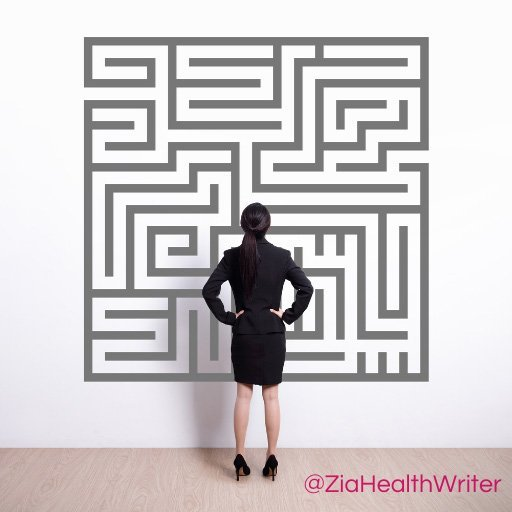 image at a smartly dressed lady stood looking a labyrinth drawing on the wall