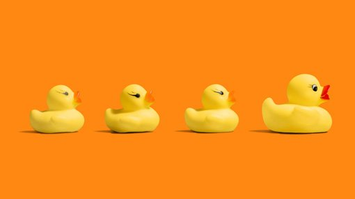 Image of mummy and 3 baby bath time ducks on an orange background